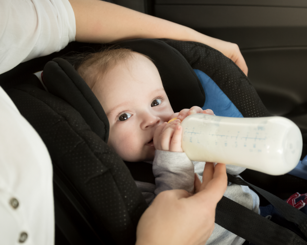 baby drinking bottle in car seat while traveling